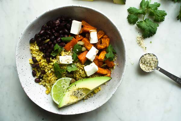 Mexican cauliflower rice in a bowl with sweet potato, lime and avocado