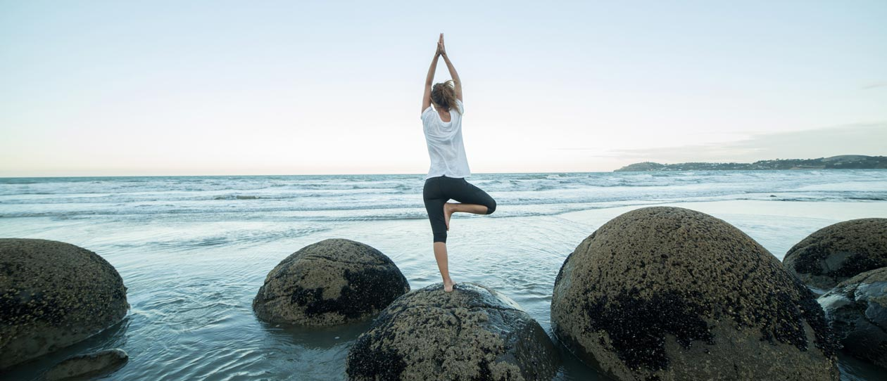 Young woman exercises doing yoga on a boulder at Moeraki boulders