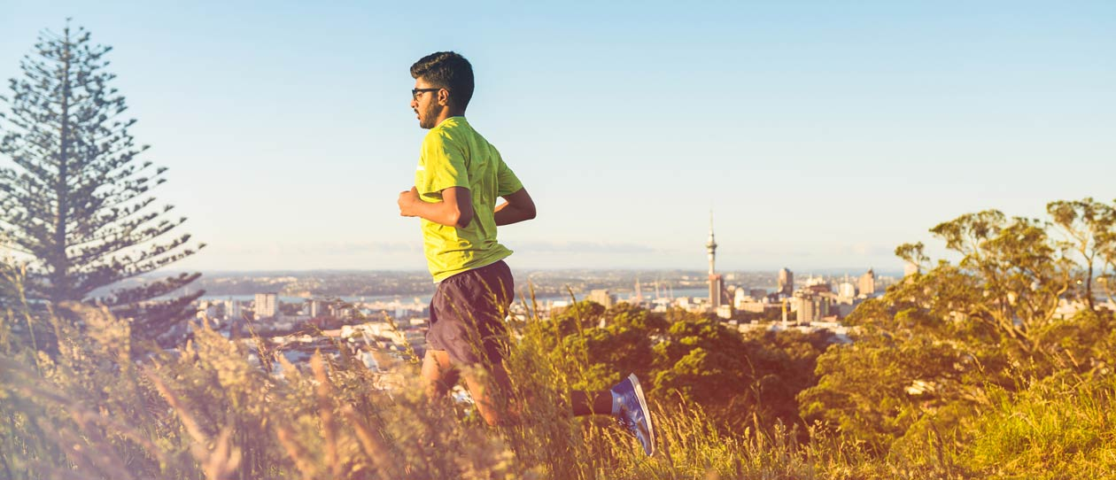 Man running on a hill in Auckland New Zealand with Sky Tower in background