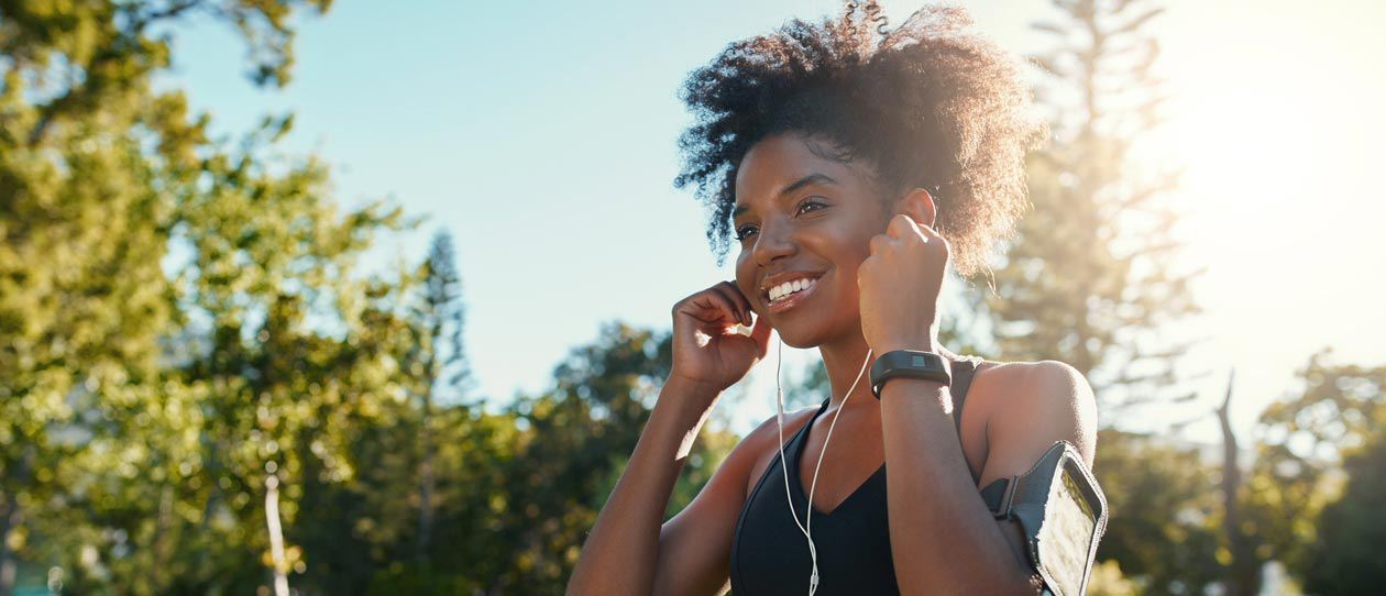 Young woman listening to music while jogging