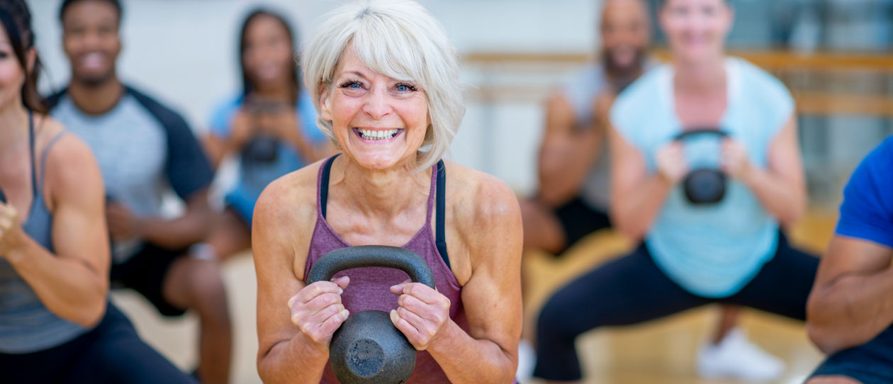 Mature woman squatting with a kettlebell in a gym class