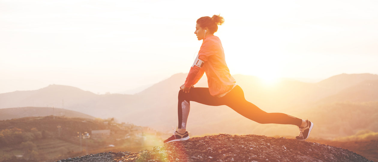 Woman stretching outdoors in the early morning before a run