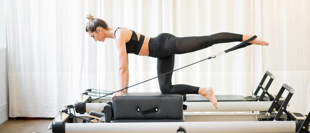 Woman exercising on a Pilates reformer